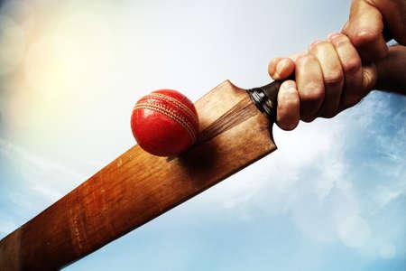 at bat: Cricket bateador golpea una pelota de tiro desde abajo contra un cielo azul