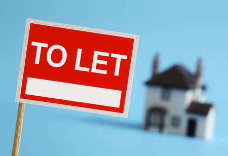 to let: Agente immobiliare a lasciare il segno con casa in background Archivio Fotografico