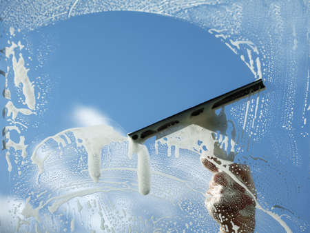 clean window: Window cleaner using a squeegee to wash a window