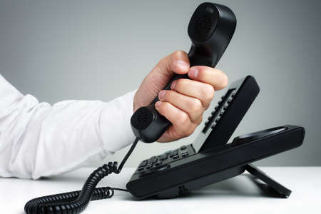 sales call: Businessman on business landline telephone in an office concept for communication, contact us and customer service support Stock Photo