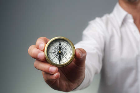 Businessman and compass showing direction concept for guidance, strategy and business orientation