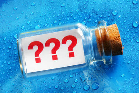 Question mark symbols message in a bottle concept for business confusion, problems and uncertainty photo