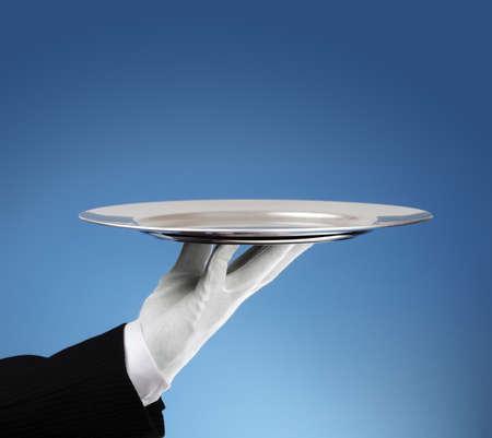 sirvientes: Camarero que sostiene una bandeja de plata vacía lista para la colocación de productos Foto de archivo