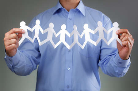 chain group: Teamwork,  community and support concept with businessman holding paper chain group of people holding hands