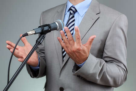 belief system: Businessman making speech with microphone and hand gesturing concept for explaining, protesting or belief