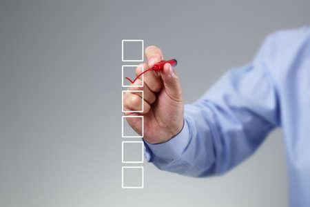 Lista de verificación en blanco en la pizarra con la mano de negocios dibujar una marca de verificación roja en una casilla de verificación