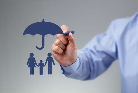 health insurance: Businessman hand drawing an umbrella above a family concept for protection, security, finance and insurance