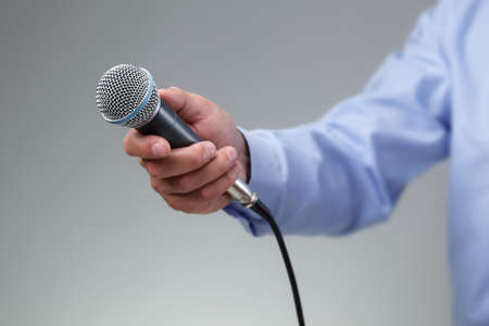 Hand holding a microphone conducting a business interview or press conference photo