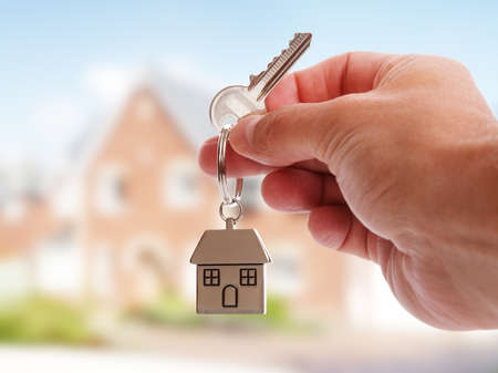 building house: Tenendo chiavi di casa su casa a forma di portachiavi di fronte a una nuova casa
