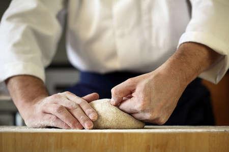 haciendo pan: Hacer pan de masa de levadura, cocinero amasando en una cocina panadería