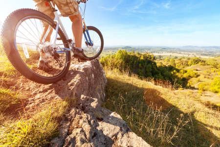 Mountain biker in action on rocks looking at downhill trail against blue sky concept for healthy lifestyle, excercise and extreme sports Stock Photo
