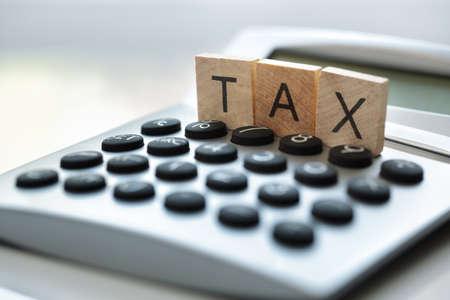 Calculator met het woord belasting geschreven in houten blokletters Stockfoto