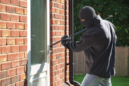 law breaking: Burglar breaking into a house via a door with a crowbar