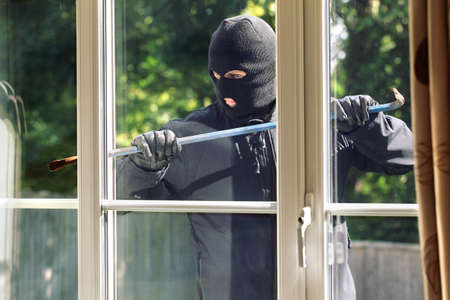 burglar: Burglar breaking into a house via a window with a crowbar