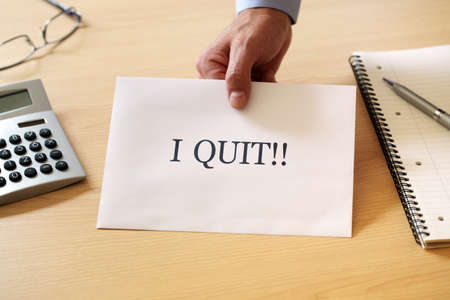 quit: Resignation letter being placed on the desk of the boss Stock Photo
