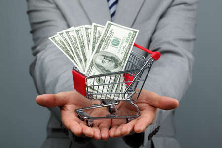 boodschappenkar: Businessman with shopping trolley full of money