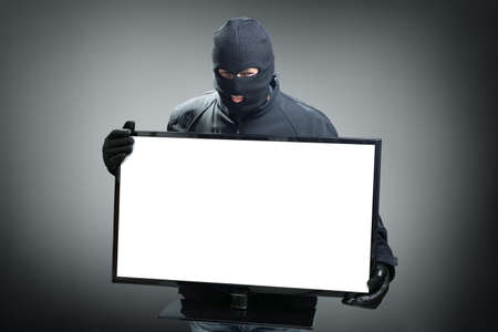 Thief stealing computer monitor or television concept for hacker, security or insurance with space on screen for message photo
