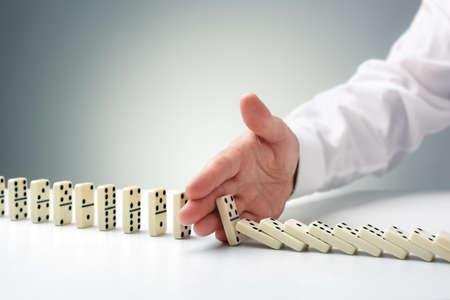 Het stoppen van het domino-effect concept voor zakelijke oplossing, strategie en succesvolle interventie Stockfoto