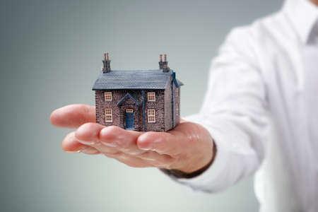 selling house: Man holding miniature model house concept for home, real estate, insurance or buying and selling property