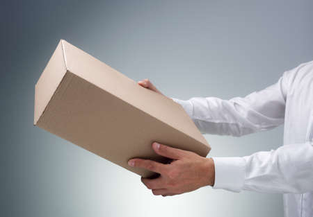 Businessman receiving or giving a cardboard box package or parcel