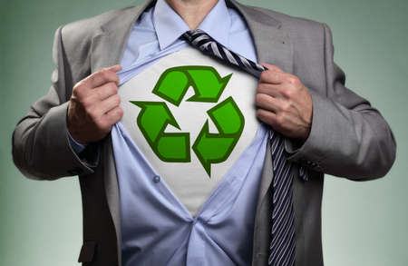 conservation: Businessman  tearing his shirt open to reveal t shirt with recycling symbol concept for recycling and environmental conservation