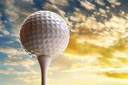 on tee: Golf ball on tee about to tee off against a sunset sky Stock Photo