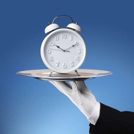 Waiter holding a silver platter with white alarm clock photo