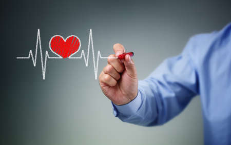 Drawing heartbeat graph on screen with a pen concept for healthy lifestyle pulse trace