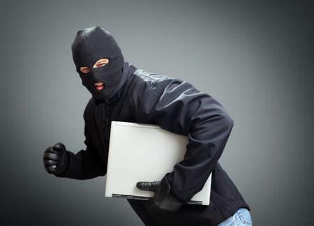Thief stealing laptop computer concept for hacker, hacking, security or insurance photo