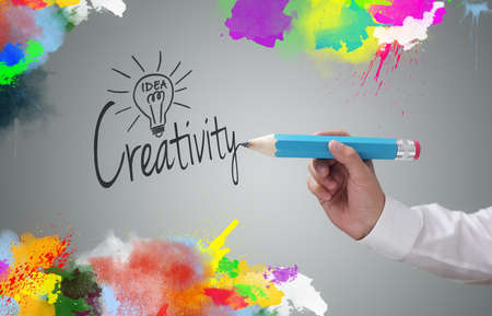 Businessman writing the word creativity and painting abstract colorful design on gray background concept for business idea, imagination and inspiration photo