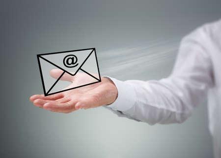 ビジネスマン、仮想エンベロープを @ 記号の電子メール、グローバル ・ コミュニケーション ・ コンセプトで保持しているメールやお問い合わせ