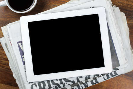 newspaper print: Digital tablet with blank screen on newspaper concept for internet and electronic news