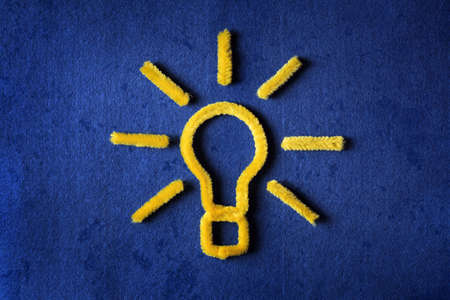 creativeness: Inspiration concept yellow pipe cleaner light bulb metaphor for good idea