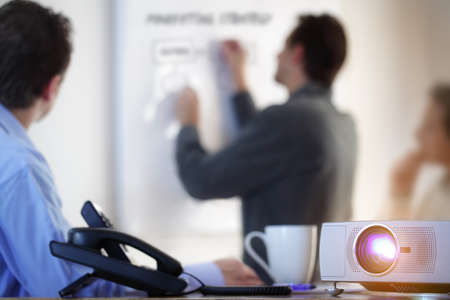 reuniones empresariales: Conferencia de negocios o una conferencia con el empresario escribiendo en la pizarra y proyector LCD en primer plano