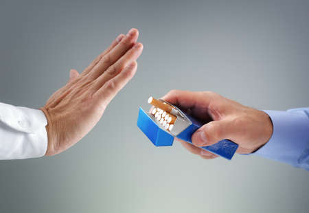 Man refusing a cigarette from a pack of smokes concept for quitting smoking and healthy lifestyle photo