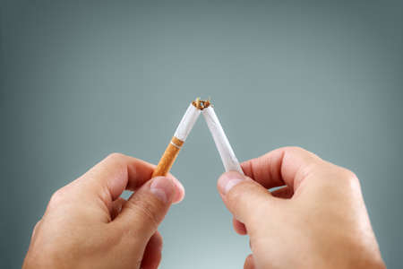 Breaking a cigarette in half concept for quitting smoking and healthy lifestyle Banco de Imagens