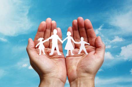 familia unida: Recorte el papel de la cadena de la familia con la protecci�n de las manos ahuecadas, el concepto de la seguridad y el cuidado
