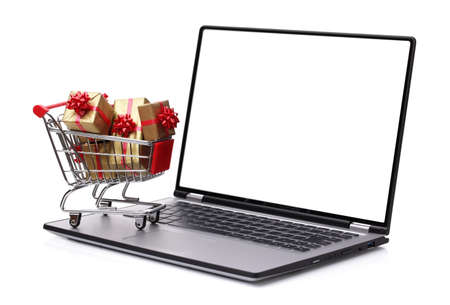 Laptop with shopping cart full of christmas or gift boxes isolated on white background with blank screen for copy photo