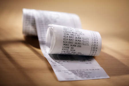 supermarket cash: Grocery shopping list till roll printout on a wooden table Stock Photo