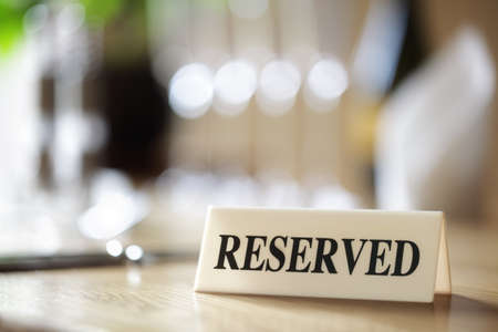 dining table: Restaurant reserved table sign with places setting and wine glasses