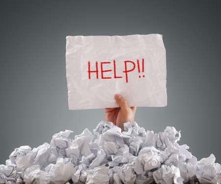 documentos: Empresario enterrado bajo pila de papeles arrugados con un cartel de ayuda