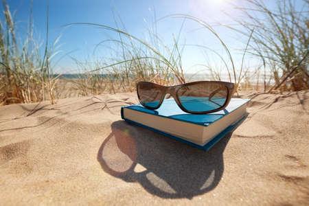 descansando: Libro y gafas de sol en la playa para la lectura de verano y relajante