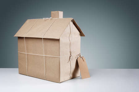 cardboard house: New house wrapped in brown paper concept for real estate, buying a new home, construction or moving house
