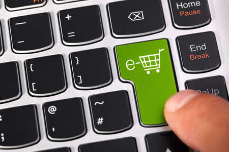 consumerism: Computer keyboard key with shopping cart icon concept for e-commerce, consumerism and internet store checkout