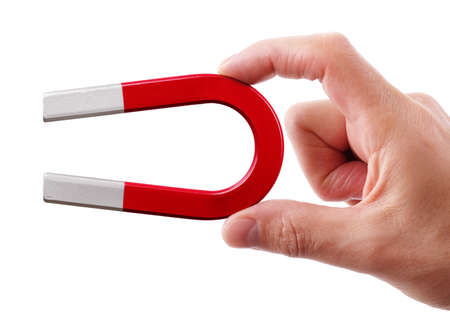 Holding a horseshoe magnet against a white background