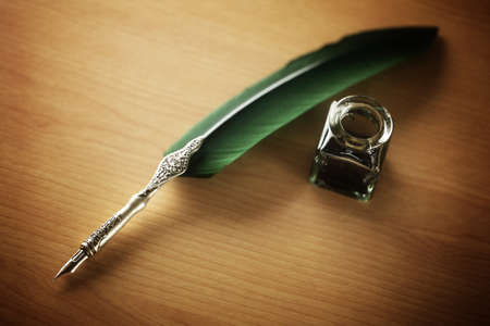 caligraphy: Quill pen and ink well resting on a desk concept for correspondence, writer, author or contact Stock Photo