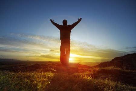 Silueta de un hombre con las manos levantadas en el concepto de la puesta del sol para la religión, el culto, la oración y la alabanza
