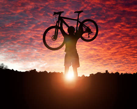 conquering adversity: Mountain biker silhouette against the sunset concept for achievement, conquering adversity and  exercising Stock Photo