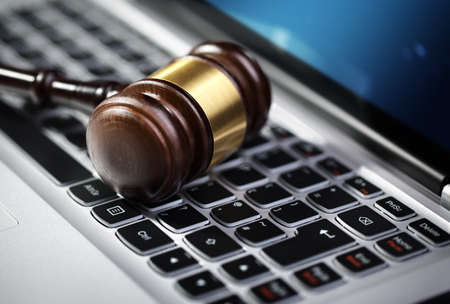 Gavel on laptop computer keyboard concept for online internet auction or legal assistance photo
