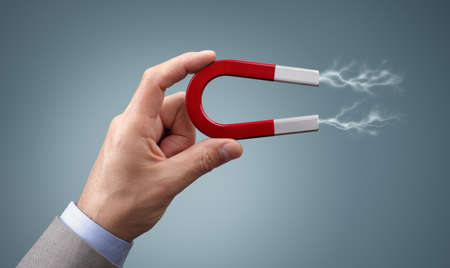 magnetism: Holding a horseshoe magnet against a gray background with magnetic field attracting